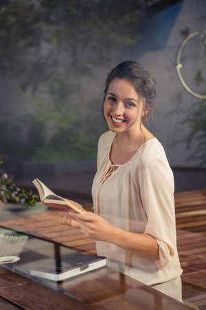 well read: Businesswoman reading a book at desk in office
