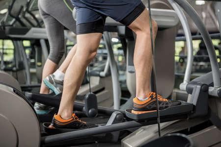 eliptica: La mujer y el hombre que ejercita en la m�quina el�ptica en el gimnasio