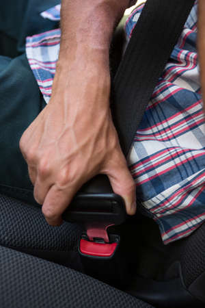 seat belt: Man putting on his seat belt in his car