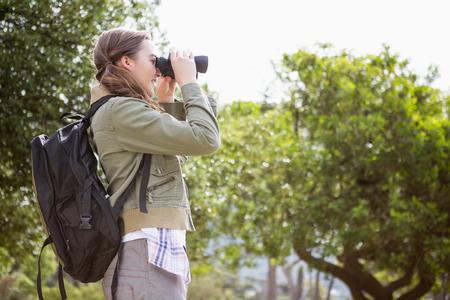 adventuring: Woman using binoculars in the countryside