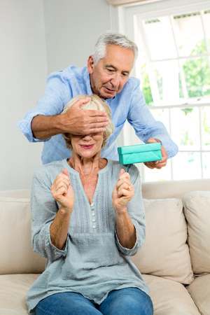 gifting: Senior man giving surprise to man by gifting at home Stock Photo