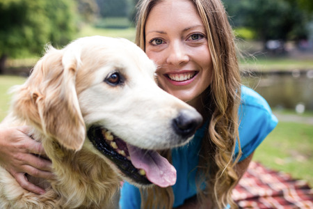 weekend activity: Portrait of a smiling woman with her pet dog in park