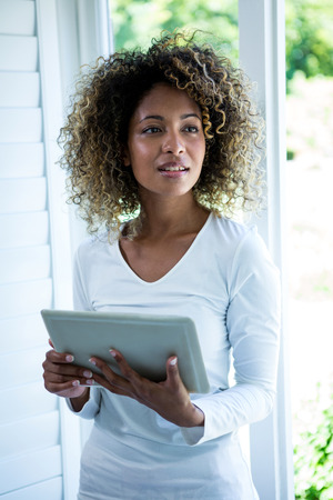 Thoughtful woman standing near the window and using a digital tablet at home Stock Photo