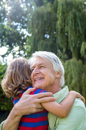 back yard: Happy grandfather hugging grandson at back yard