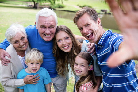 multigeneration: Multi-generation family posing for a selfie in the park on a sunny day Stock Photo