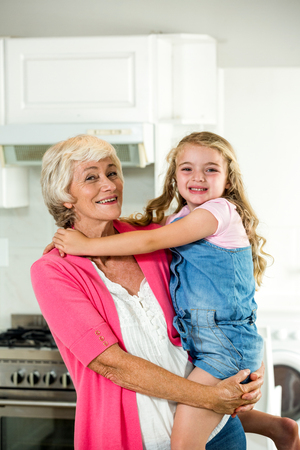 carrying girl: Portrait of happy granny carrying girl while standing in kitchen