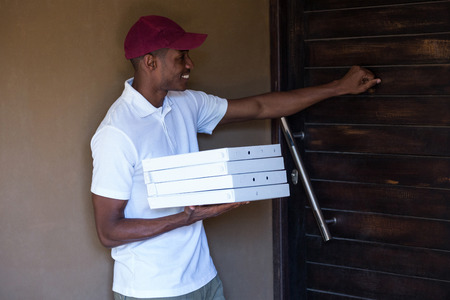 knocking: Pizza delivery man with pizzas boxes knocking a door Stock Photo