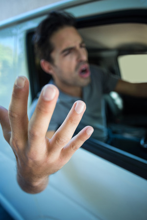 wrath: Angry young man gesturing while sitting in car