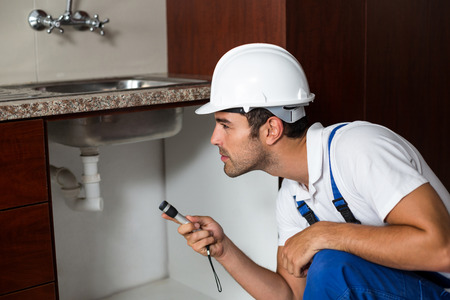 kneeling: A Man is using torch while kneeling in kitchen Stock Photo