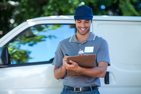 person writing: Smiling delivery person writing in clipboard while standing by van Stock Photo