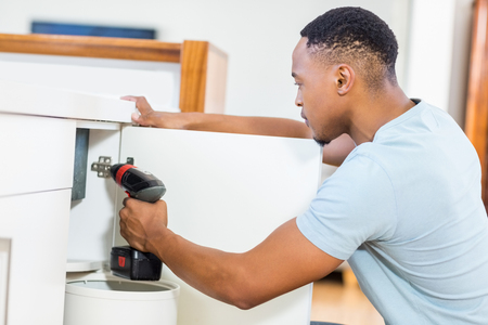 man power: Man drilling a hole inside the cabinet at home Stock Photo