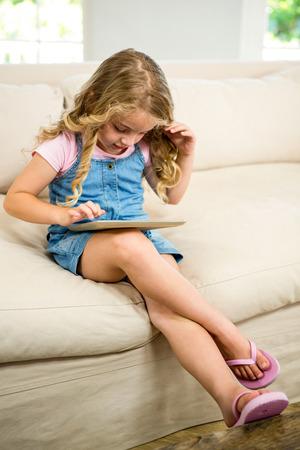 legs crossed at knee: Cute girl using digital tablet while sitting on sofa