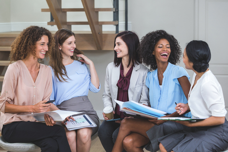 interacting: Female business colleagues interacting with each other in office Stock Photo
