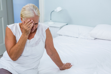 Upset senior woman touching head on bed at home Stock Photo