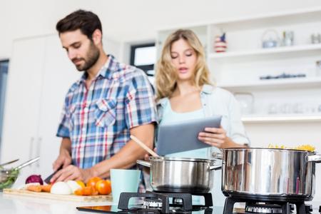 Pareja joven cortar verduras y usa la tableta digital en la cocina