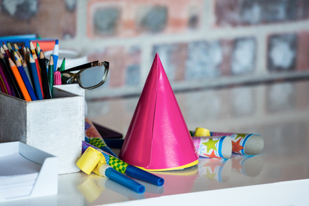 pen holder: Party horn, birthday hat, pen holder and spectacle on desk in office Stock Photo