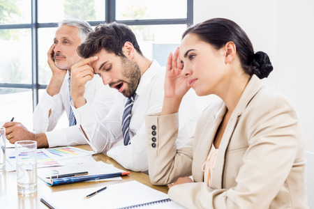 disinterested: Business colleagues getting bored in a meeting at office Stock Photo