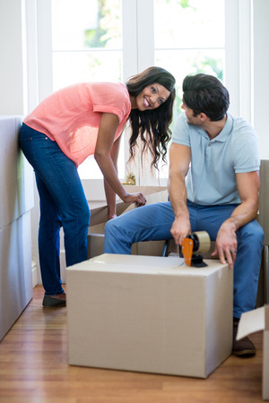 sealing tape: Young couple assisting each other while unpacking carton boxes in new house Stock Photo