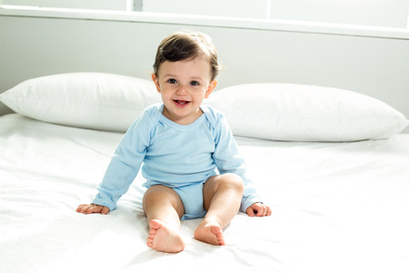 looking at baby: Portrait of cute baby boy sitting on bed at home