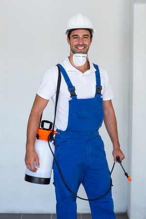 crop sprayer: Portrait of happy manual worker with insecticide standing against wall