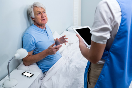 tablet: Nurse holding digital tablet while discussing with senior man at hospital