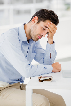 tensed: Tensed businessman sitting at table with hand on forehead in office