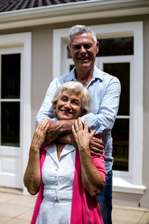 arms around: Smiling senior couple standing with arms around outside house at yard