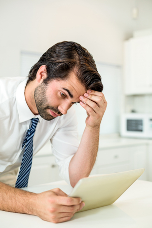 tensed: Close-up of tensed businessman looking at digital tablet by table in kitchen