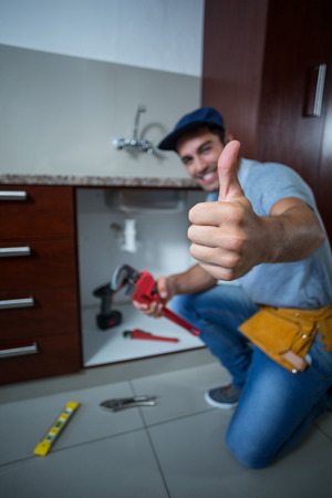 pipe wrench: Portrait of happy man showing thumbs up while holding pipe wrench in kitchen