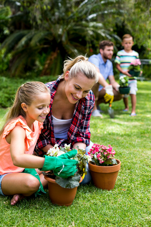 flower pots: Mother with daughter holding flower pots against family at yard