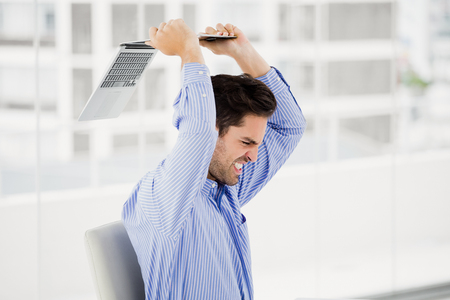 violence in the workplace: Frustrated businessman throwing laptop in office