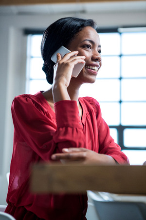 woman at the phone: Woman talking on mobile phone in office Stock Photo