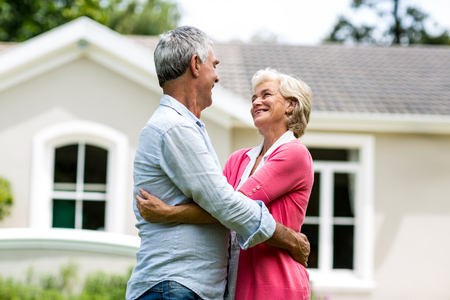 arms around: Smiling senior couple with arms around against house at yard Stock Photo