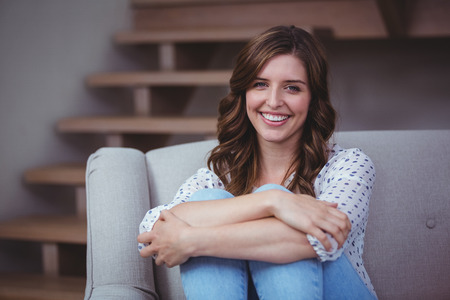 hugging knees: Portrait of beautiful woman sitting on sofa in living room