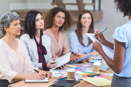 noting: Woman noting on clipboard while colleagues listening presentation in office Stock Photo