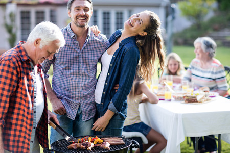 barbecue grill: Couple and a senior man at barbecue grill preparing a barbecue in garden Stock Photo