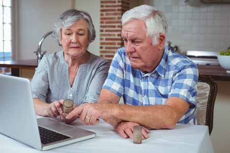 finding a cure: Senior couple searching pills with help of laptop while sitting at table