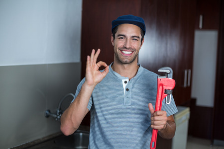 pipe wrench: Portrait of happy man showing ok sign while holding pipe wrench in kitchen