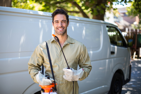 crop sprayer: Portrait of smiling worker with pesticide sprayer while standing by van