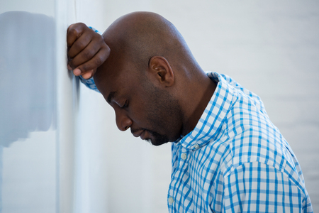 hand on forehead: Upset man with eyes closed and hand on the forehead leaning against a wall in office Stock Photo