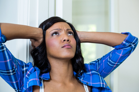 tensed: Tensed woman with hand on head at home