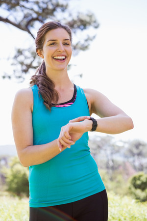 adventuring: Smiling woman checking her watch in the countryside