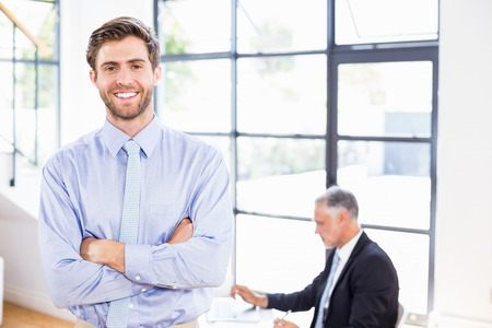 crossing arms: Smiling businessman crossing arms in front of working businessman in office