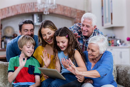 video chat: Multi-generation family waving hands while using digital tablet for video chat at home
