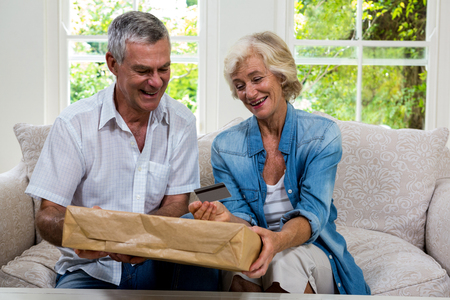 debit card: Happy senior couple holding parcel and debit card in sitting room at home Stock Photo