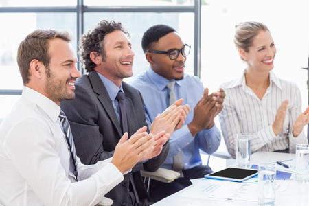 applauding: Businesspeople applauding while in a meeting at office