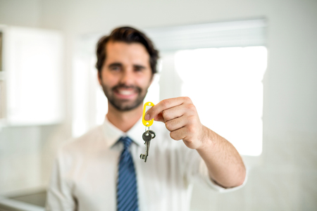 classy house: Confident businessman showing key while standing at home
