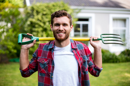 weekend activity: Portrait of smiling man carrying rake while standing in yard Stock Photo