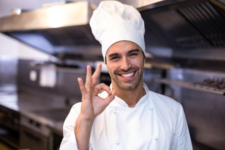 commercial kitchen: Handsome chef showing ok sign in a commercial kitchen