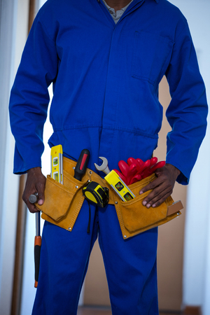 handy man: Mid section of handy man wearing tool belt at home Stock Photo